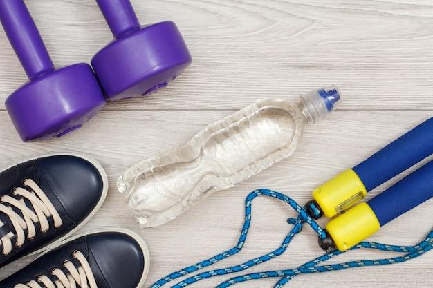 Diversi strumenti per il fitness con bottiglia d'acqua in camera o in palestra su pavimento grigio