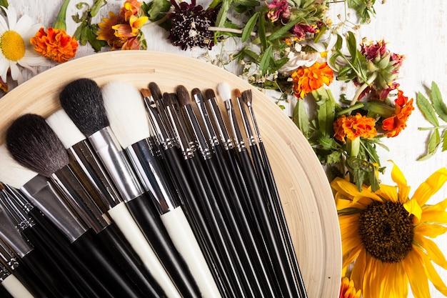 Diversi tipi di pennelli per il trucco su un piatto accanto a fiori selvatici su fondo di legno