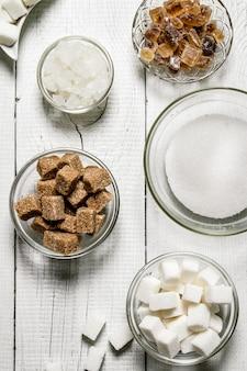 Diversi tipi di zucchero di canna e bianco in tazze sul tavolo di legno bianco.
