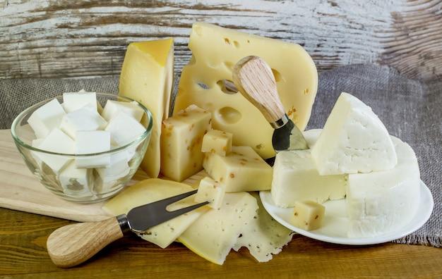 Diversi tipi di formaggio e coltelli speciali sul tavolo di legno