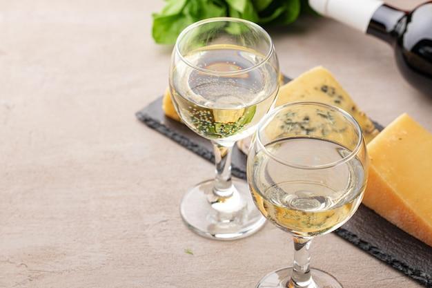 Diversi tipi di formaggio e vino serviti sulla tavola grigia