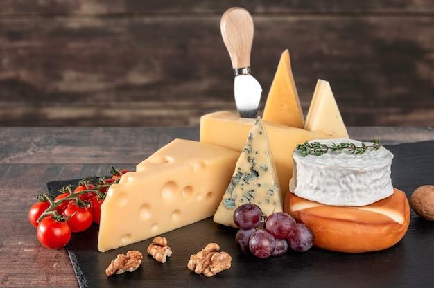 Diversi tipi di formaggio con noci e uva sul bordo di ardesia nera su fondo di legno rustico