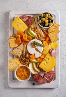 Diversi tipi di formaggi e salumi. vista dall'alto su uno sfondo bianco. formaggi assortiti con noci, cracker, olive, salame e rosmarino.