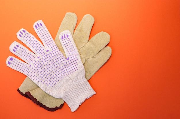 Diversi tipi di guanti da costruzione su uno sfondo arancione brillante. mezzi di protezione e sicurezza. copia spazio per il testo.