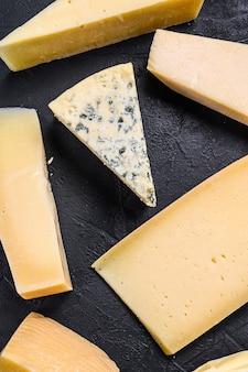 Diversi tipi di deliziosi formaggi. sfondo nero. vista dall'alto