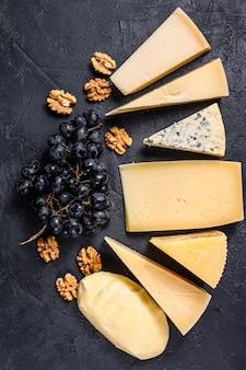 Diversi tipi di deliziosi formaggi con noci e uva. sfondo nero. vista dall'alto