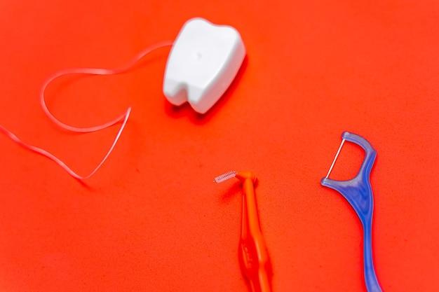 Diversi tipi di filo interdentale e stuzzicadenti su sfondo rosso. filo interdentale a forma di giocattolo del dente.