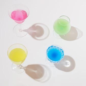 Diversi tipi di bevanda. rosa, giallo, blu e verde mix di colori estivi. un concetto positivo per le feste estive e il divertimento in spiaggia.