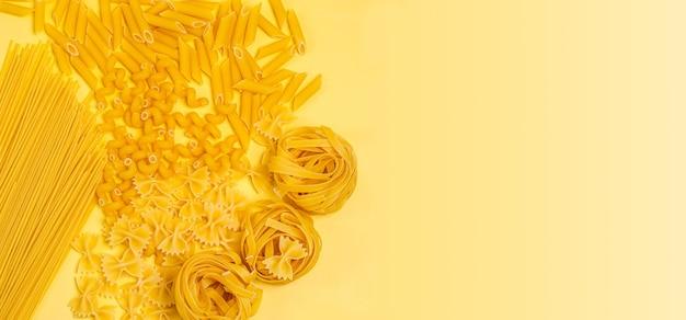 Diversi tipi di pasta secca italiana sotto forma di una cornice rotonda su uno sfondo giallo
