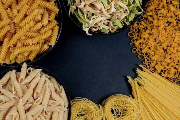 Diversi tipi di pasta secca sul piatto e in ciotole su sfondo nero. spazio per il testo, vista dall'alto.