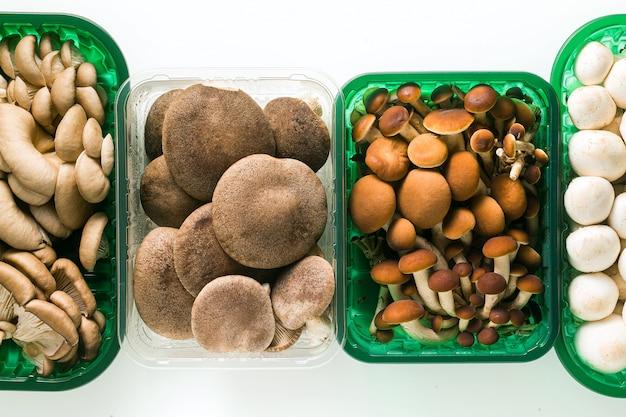 Diversi tipi di funghi freschi in imballaggi in plastica isolati sul tavolo bianco