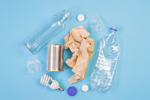 Diversi tipi di immondizia su sfondo blu