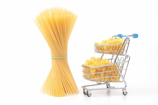 Diversi tipi di pasta italiana in un cesto della spesa dal mercato su sfondo bianco. prodotti di farina e cibo in cucina