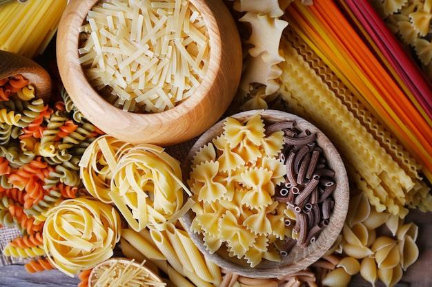 Diversi tipi di pasta con ciotole di legno sul tavolo, vista macro