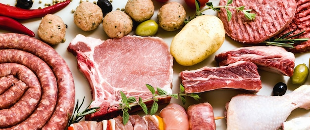Diversi tipi di rabanner di diversi tipi di carne cruda: cosce di pollo, hamburger di maiale e manzo, costolette e spiedini, polpette di tacchino, pronte per essere cucinate con patate,