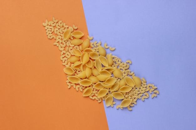 Diversi tipi di pasta italiana cruda su sfondo marrone viola.