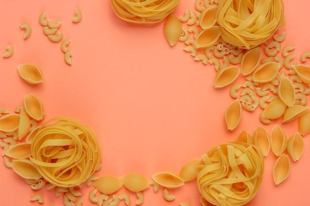Diversi tipi di pasta italiana cruda su sfondo color corallo.