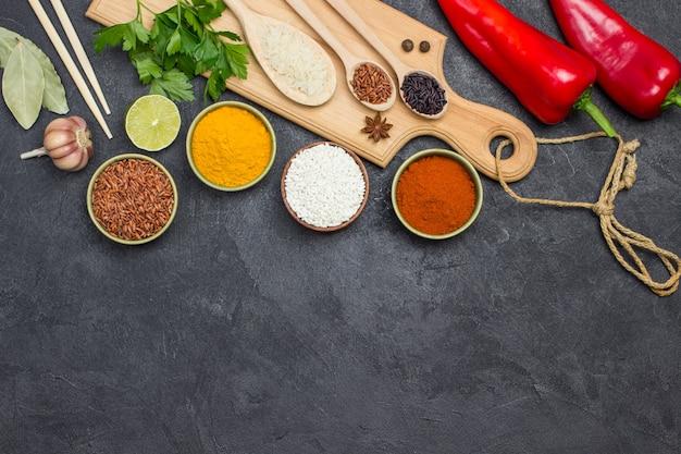 Diversi tipi di riso e spezie. tagliere in legno. pepe rosso crudo. copia spazio. lay piatto. sfondo nero