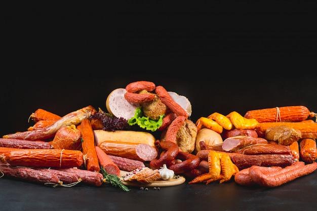 Diversi tipi di salsicce e prodotti a base di carne sul nero.