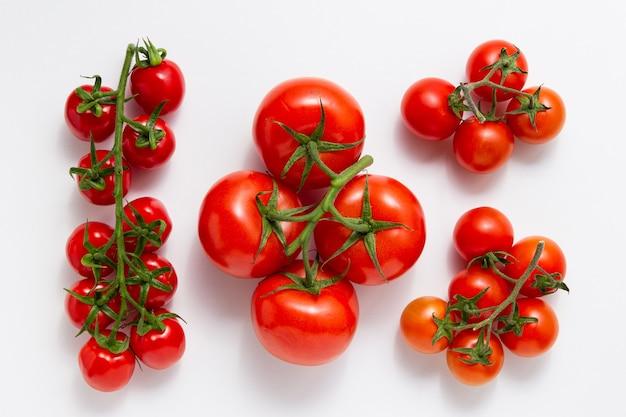Diversi tipi di pomodori su sfondo bianco. vista dall'alto di verdure fresche.