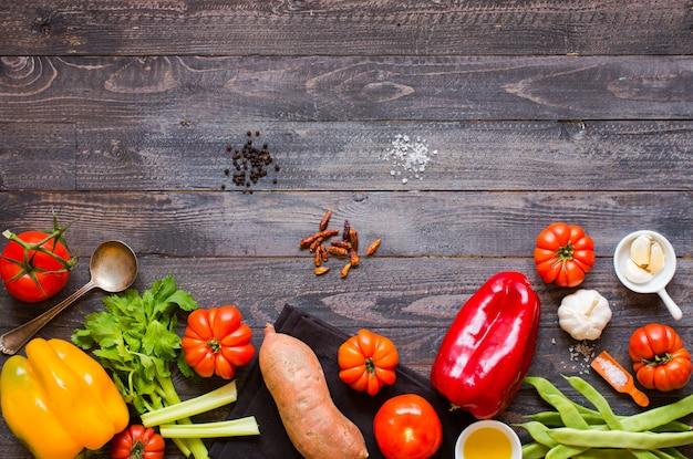 Diversi tipi di verdure, su un vecchio tavolo di legno, spazio per il testo.