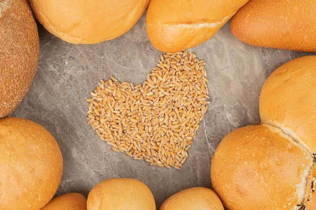 Diversi tipi di pane bianco e marrone con semi su una superficie di pietra