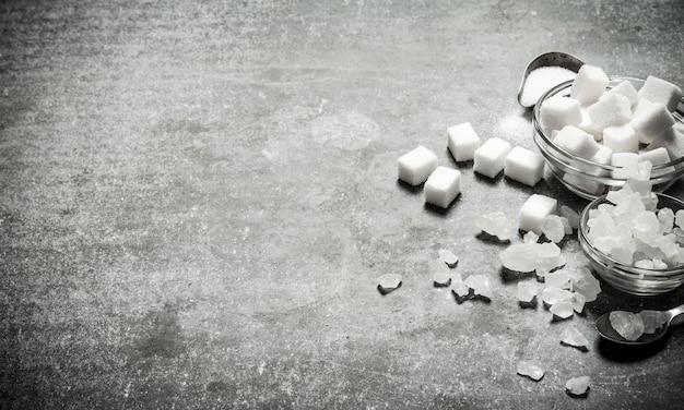 Diversi tipi di zucchero bianco in un bicchiere e un cucchiaio. su uno sfondo di pietra.