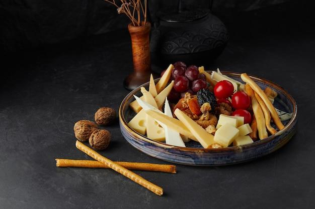 Diverse varietà di formaggio e pomodori su un piatto grande su sfondo nero