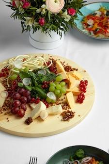 Diverse varietà di formaggio con noci e uva.