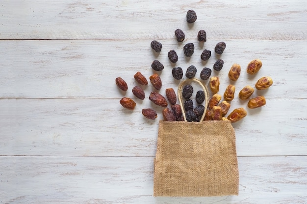 Diverse varietà di datteri sono disposte su un tavolo di legno con una borsa.