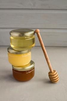 Diverse varietà di miele in piccoli barattoli di vetro sul tavolo grigio. avvicinamento.