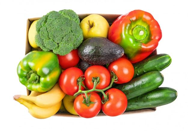 Diverse verdure, frutta in una scatola di cartone su bianco, vista dall'alto.