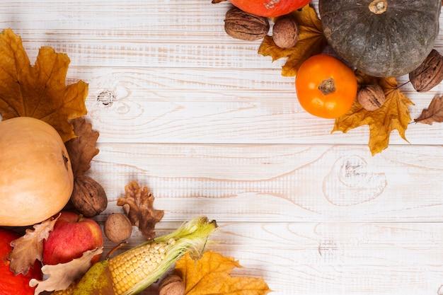 Diverse verdure, zucche, mele, pere, noci, mais, pomodori e foglie secche su fondo di legno bianco. autumn harvest, copyspace.