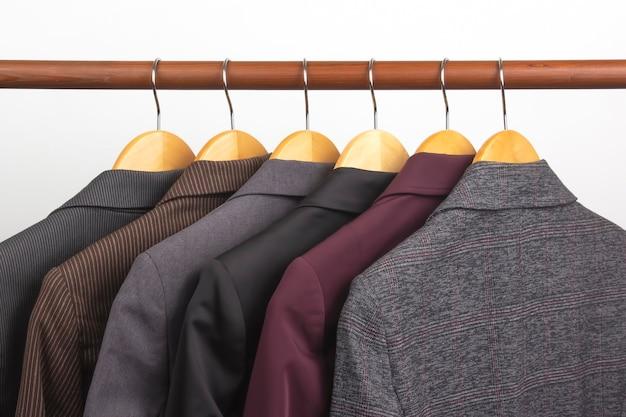 Diverse giacche classiche da ufficio da donna sono appese a una gruccia per riporre i vestiti. la scelta dello stile di vestiti alla moda