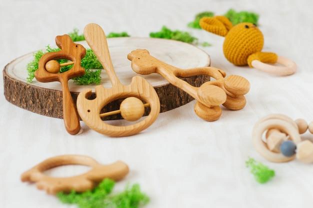 Giocattoli di massaggiagengive per bambini organici in legno diversi su sfondo chiaro con dettagli naturali