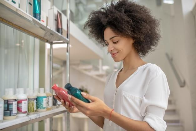 Difficoltà di scelta. giovane donna sorridente premurosa con cosmetici di cura nelle mani al centro di bellezza