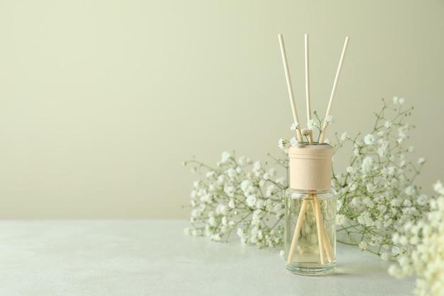 Diffusore e fiori su tavolo strutturato bianco