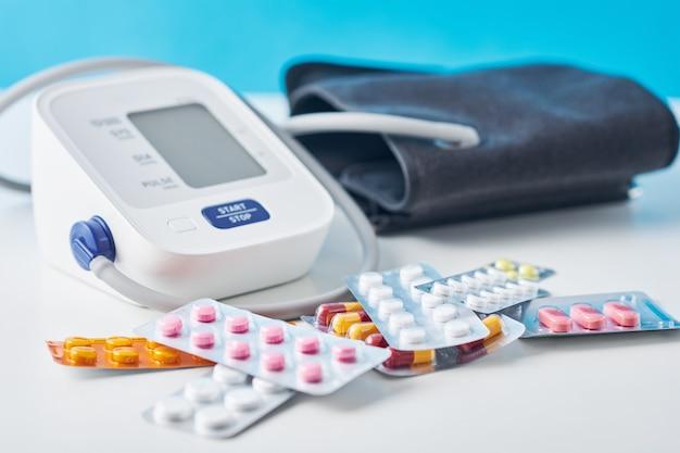 Monitor di pressione sanguigna di digital e pillole mediche sulla tavola bianca. concetto di sanità e medicina