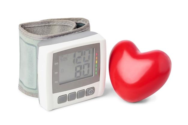 Monitor digitale della pressione sanguigna (tonometro) con cuore rosso decorativo vicino, isolato su sfondo bianco.