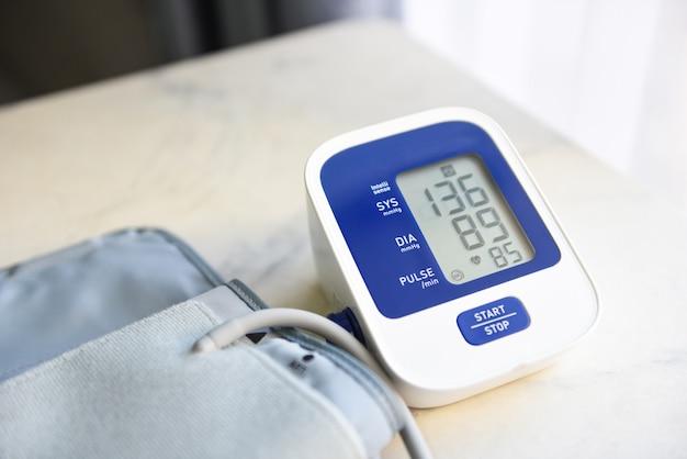 Monitor digitale della pressione sanguigna sulla tavola di legno, tonometro elettronico medico controlla la pressione sanguigna