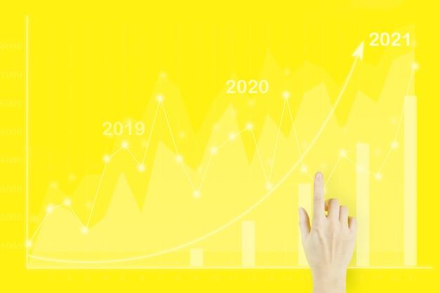 Affari digitali e mercato azionario. la mano di una giovane donna che punta il dito con grafici finanziari olografici che mostrano entrate in crescita nel 2021 su sfondo giallo.