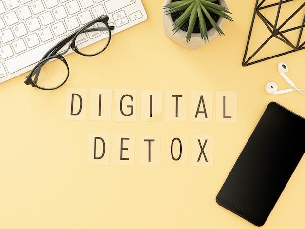 Parole di disintossicazione digitale su una scrivania da lavoro minimale con gadget e pianta