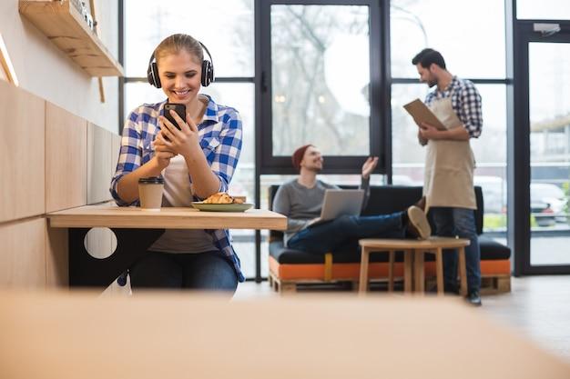 Dispositivo digitale. gioiosa bella donna positiva seduta al tavolo e utilizzando il suo gadget mobile mentre ha uno schiaffo nel caffè