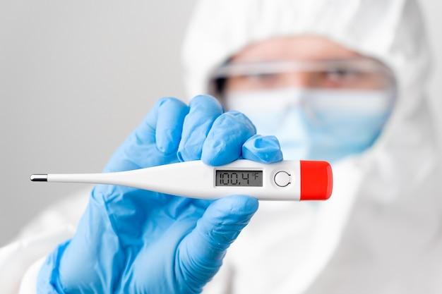 Termometro digitale o elettronico con alta temperatura 100,4 fahrenheit nelle mani del medico, dottore o