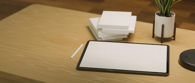 Tavoletta grafica digitale computer mockup schermo vuoto con libri penna stilo e pianta su tavola di legno