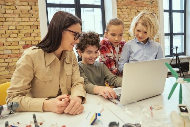 Alfabetizzazione digitale: i bambini intelligenti imparano a programmare utilizzando il laptop seduti al tavolo in un'aula