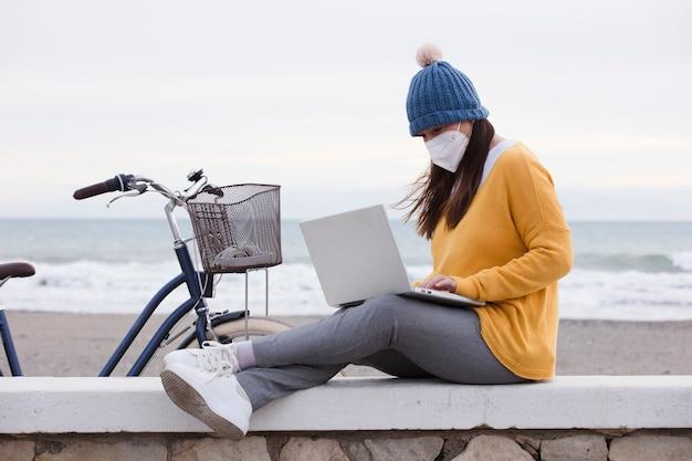 Un marketer digitale che indossa una maschera per il viso sta lavorando a un nuovo laptop