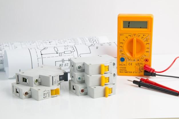 Multimetro digitale e interruttore con disegni cartacei sul tavolo bianco