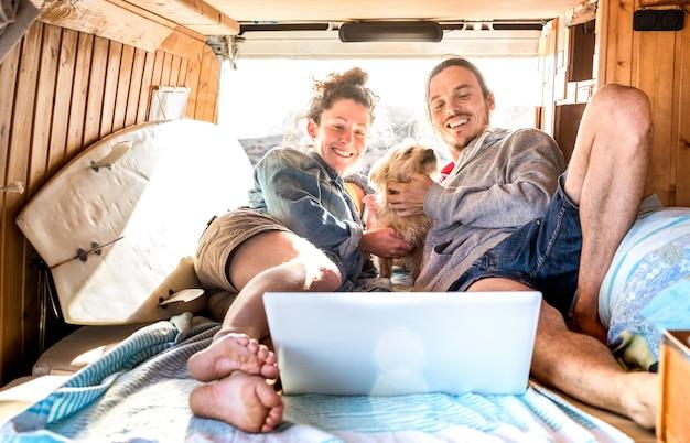 Coppia nomade digitale con cane carino utilizzando laptop su trasporto mini van retrò - concetto di ispirazione per la vita di viaggio con persone indie su viaggio avventura in minivan guardando il pc in un momento di relax - filtro caldo