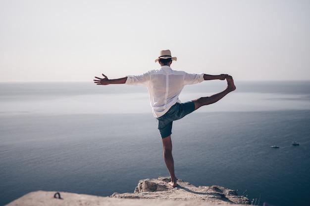 Un nomade digitale un uomo con un cappello un uomo d'affari fa yoga sugli scogli in riva al mare all'ora del tramonto fa a